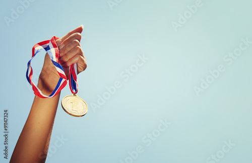 Fotografie, Tablou  woman hand raised, holding gold medal against sky