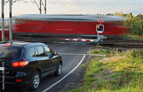 Speeding motion blur red train passing through a railway crossing with gates Canvas-taulu