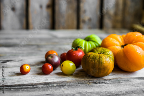 Fotografie, Obraz  Colorful heirloom tomatoes on rustic wooden background
