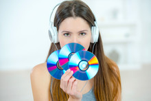 Lady With Headphones Holding Three CDs