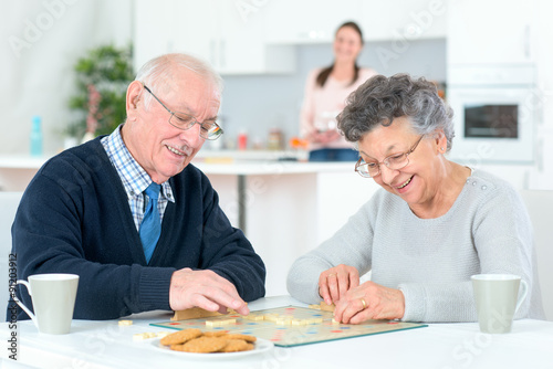 Grandparents playing a board game плакат