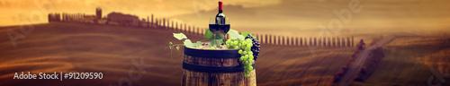 Fotografia  Red wine bottle and wine glass on wodden barrel. Beautiful Tusca
