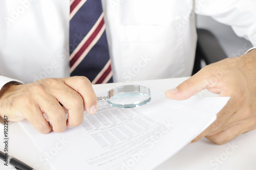 Fotografia  Businessman with magnifying glass reading documents