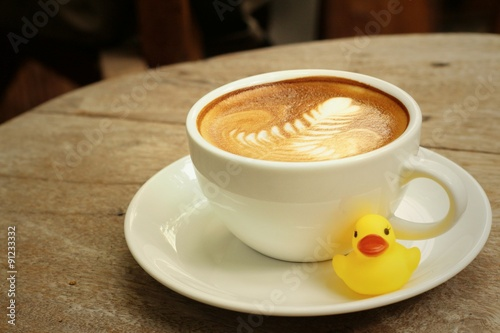 Staande foto Thee latte coffee with yellow rubber duck on background of wooden.
