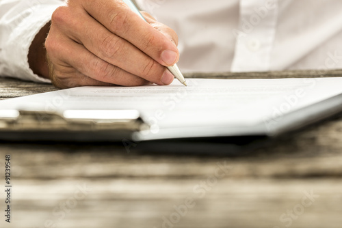 Fotografía  Closeup low angle view of male hand signing subscription form, l