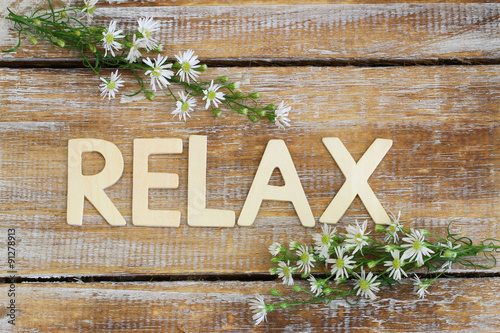 Deurstickers Ontspanning Relax written on rustic wood and chamomile flowers