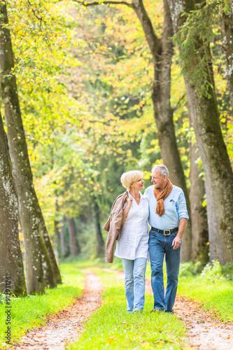 Tuinposter Zwavel geel Älteres Paar macht Spaziergang im Wald