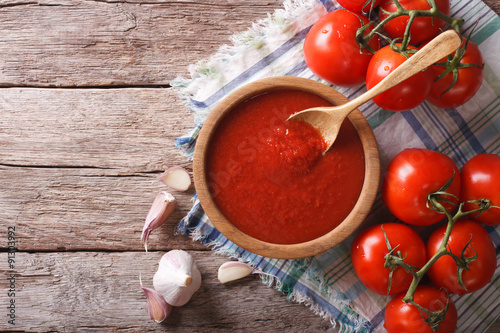 tomato sauce with garlic and basil in a wooden bowl. horizontal top view