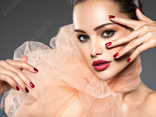 Poster  closeup face of a fashion woman with stylish makeup, red nails a