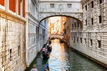 Tourists In Gondolas Sailing Under The Bridge Of Sighs, Venice