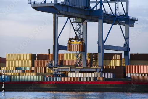 Fotografia  Suwnica bramowa podnosząca kontener ze stosu do barki