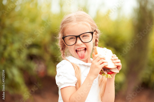 Fototapeta Funny kid girl eating sandwich outdoors. Having fun. Looking at camera. Posing over nature background. Healthy food. Childhood.  obraz