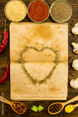 Open old vintage book with spices and heart on wooden background open old vintage book with spices and heart on wooden background healthy vegetarian food forumfinder Images