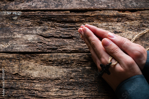 man praying with a cross in his hands on a wooden background
