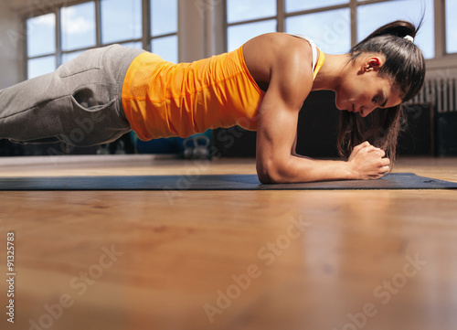 Photo  Muscular female doing core workout in the gym