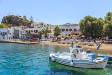 Greek Island Of Patmos Belongs To The Dodecanese. Fragment Of The Fishing Port And Beach In The Town Of Skala. On The Hill Visible Town Chora And Monastery Of St. John's