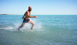 A strong man, athletic, running fast on the sea with a naked torso