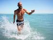 Bald elderly man runs along the ocean with a naked torso