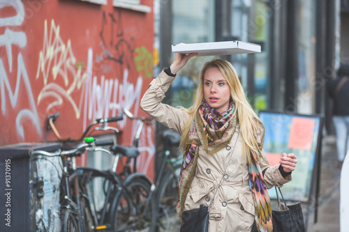 Photo Woman under the rain covering with a pizza in Copenhagen