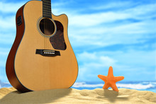 Acoustic Guitar And Starfish On The Beach With Blue Sea And Sky