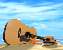 Acoustic Guitar On The Sandy Beach In Summer With Blue Sea And Sky