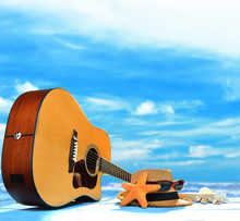 Acoustic Guitar On The Beach With Blue Sea And Sky