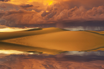 Fototapeta na wymiar Reflection of the sunset sky and sand dunes in the water.
