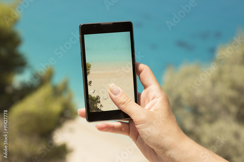 Fotomural Taking a snapshot of a beautiful beach with a cellphone