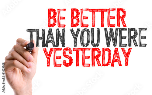 Photo  Hand with marker writing: Be Better Than You Were Yesterday