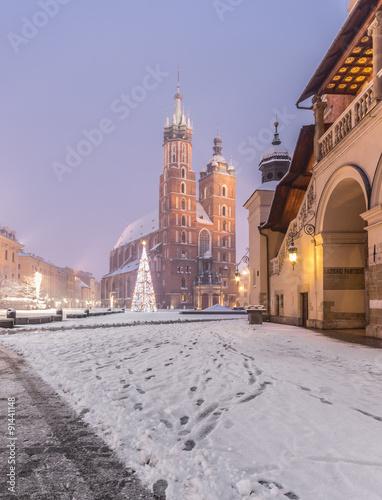 Fototapeta Krakow, Poland, St Mary's church and Sukiennice (Cloth hall) on the Main Market Square in heavy snow obraz