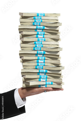 Fotografie, Obraz  Hand of a business man holding a tall stack of money