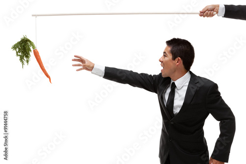 Fototapeta Businessman reaching for a carrot at the end of a stick obraz
