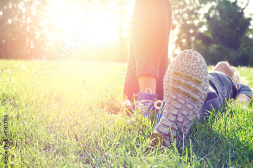 Female athlete resting and relaxing after workout. Woman lying down on grass. Healthy lifestyle and happiness concept