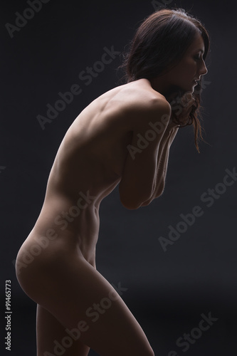 Foto  Art portrait of a nude brunette in the studio.