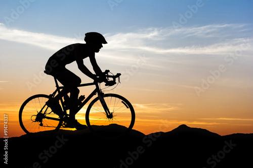 Fototapeta Muž na kole na hory na soumraku
