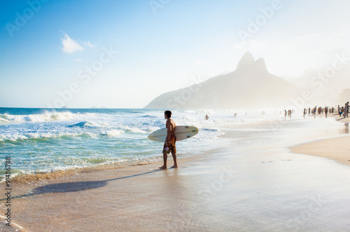 Fotomural  Brazilian surfer walking with surfboard toward Two Brothers Moun