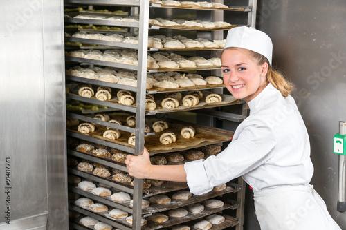 Obraz na plátně Baker at bakery putting rack of fresh dough in refrigerator