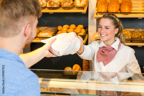 Poster Boulangerie Shopkeeper in bakery hand bag of bread to customer