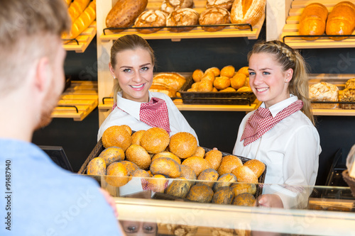 In de dag Bakkerij Two shopkeepers presenting a basket with buns to client