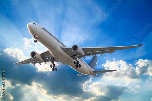 Tuinposter Vliegtuig Commercial airplane flying with clouds and sun rays background