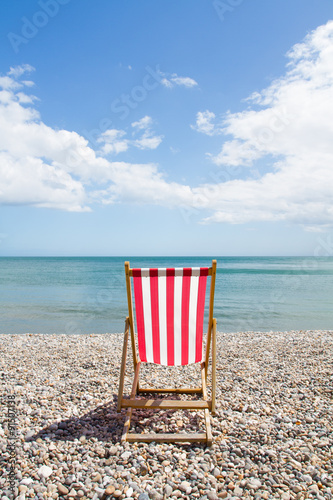Photo A single red, striped deckchair sits on a pebble beach on a sunny day