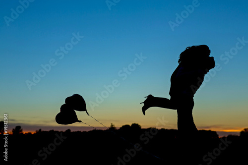 Fotografia  Passionate silhouette of an engaged couple kissing with a beautiful sky sunset,