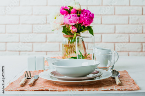 Fotografía  Beautiful table setting with flowers in vase on brick wall background