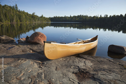 Yellow canoe on rocky shore of calm lake with pine trees Fototapete