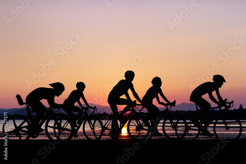 People cycling at beach Poster