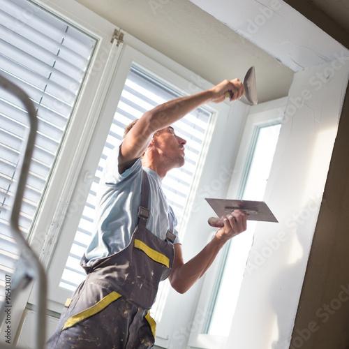 Plasterer renovating indoor walls and ceilings.