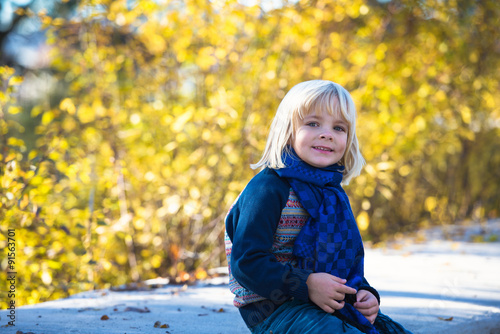 Portrait of adorable cute boy  in the beauty autumn park Poster Mural XXL
