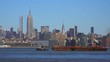 A tugboat pulls a barge on the Hudson River in New York City with the Empire State Building background.