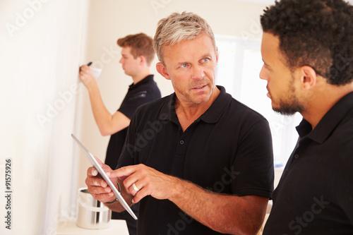 Fotografie, Obraz  Decorator instructing colleague painting a room