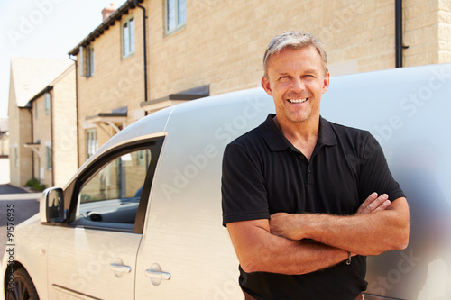 Portrait of middle aged tradesman standing by his van